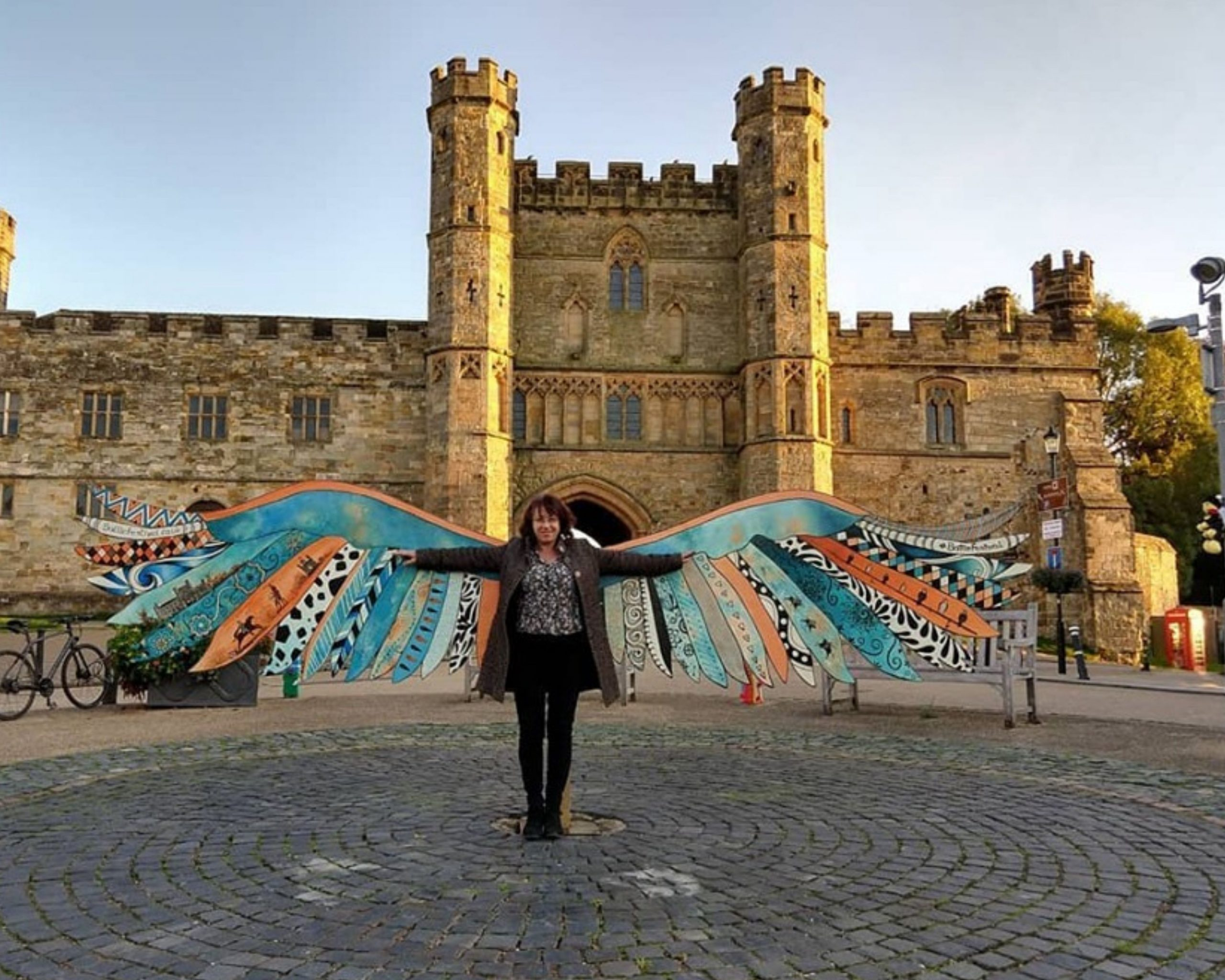 Woman with wings standing in front of castle gates