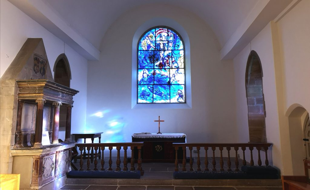 The interior of All Saints Tudeley showing Chagall's stained glass window