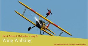 Wing walker on the top wing of a biplane